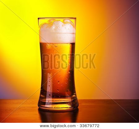 Glass of refreshing beer on wooden table, closeup on cold alcoholic drink over yellow background, food still life, party lifestyle, celebrating Oktoberfest holiday, traditional German lager