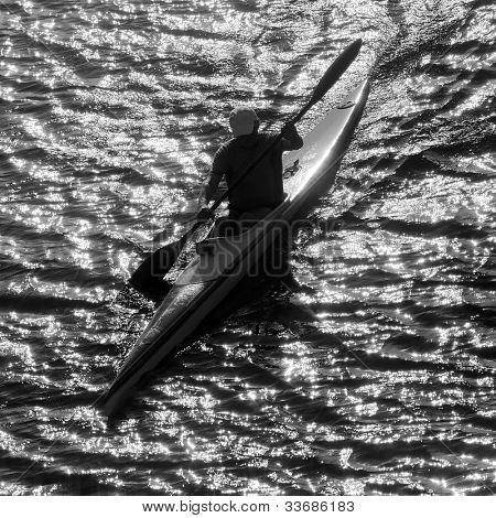 Silhouette of man kayaking in the lake at sunset. Classical black and white photography of high contrast scene.