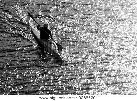Silhouette of a man kayaking in the lake at sunset. Classical black and white photography of high contrast scene.