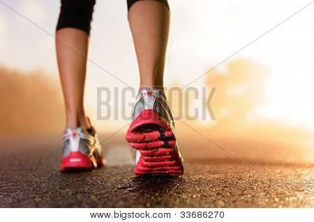 Pies de corredor en carretera closeup en Zapata. concepto de mujer fitness sunrise jog entrenamiento Wellness.