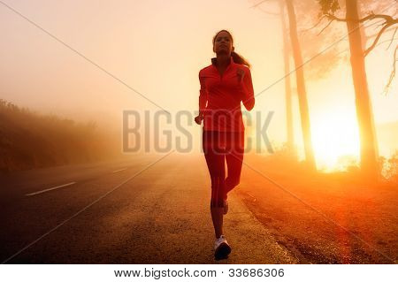Healthy running runner woman early morning sunrise workout on misty mountain road workout jog. sunflare through the mist gives atmospheric feel and depth to these fitness images