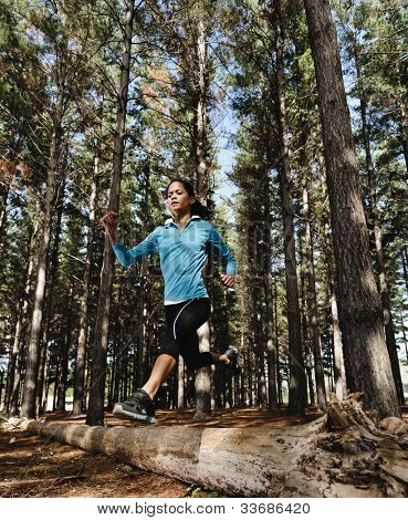 trail running jump fitness woman training alone outdoors in the forest