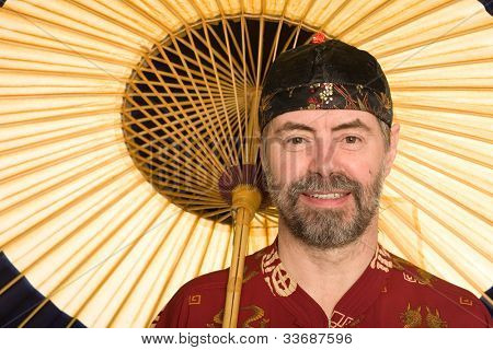 Caucasian in traditional Chinese shirt holding an umbrella. Umbrella is made of bamboo and paper.