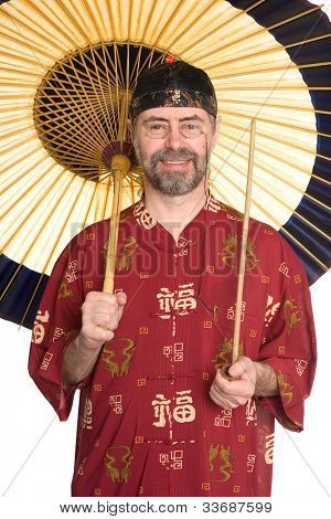 Caucasian in traditional Chinese shirt holding pipe. Umbrella is made of bamboo and paper.