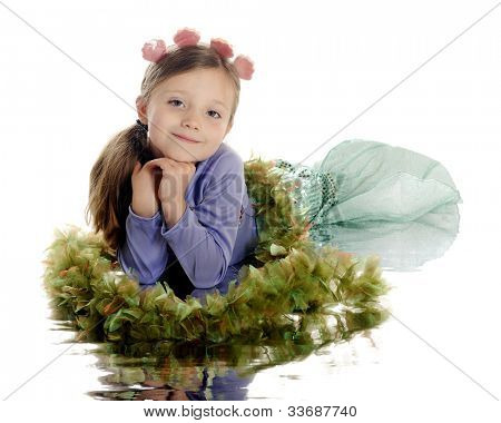 "A beautiful elementary girl posed as a mermaid on ""sea weed"" and with a watery reflection.  On a white background."