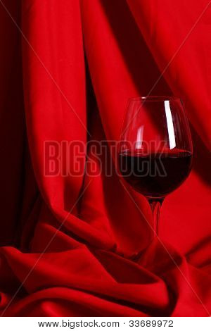 Glass of red wine over red cloth