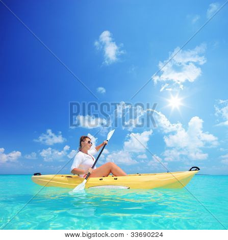 Woman kayaking on a sunny day, Kuredu island, Maldives, Lhaviyani atoll