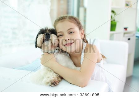 Portrait of happy girl holding shih-tzu dog and looking at camera