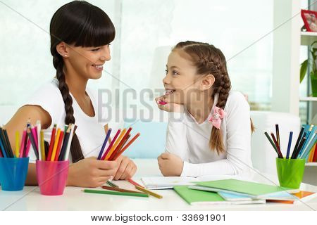 Portrait of lovely girl looking at her mother while drawing with colorful pencils