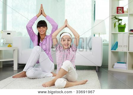 Portrait of little girl and her mother doing yoga exercise at home