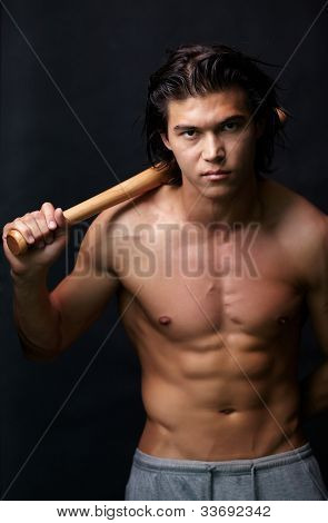 Image of shirtless man with bat looking at camera