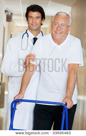 Young happy doctor helping an old man with his walker