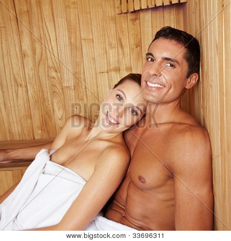 Attractive happy couple relaxing together in a sauna