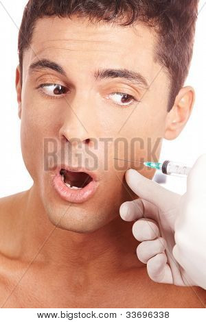Attractive man is afraid of a needle and syringe