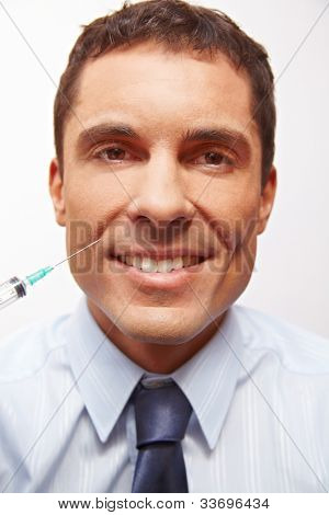 Smiling business man at wrinkle treatment getting needle in corner of mouth