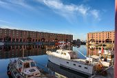 Boats Moored In The Albert Dock, Liverpool On A Beautiful Sunny Day. The Old Buildings Are Reflected poster