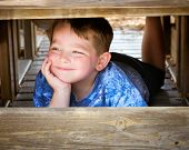 Happy smiling boy playing and hiding from his friends on playground