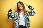 Young beautiful woman wearing casual jacket over yellow isolated background smiling pointing to head poster