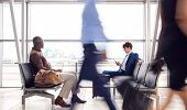 Business Passengers Sitting In Busy Airport Departure Lounge Using Mobile Phones poster