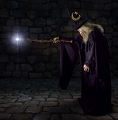 stock photo of merlin  - Wizard in a purple robe and wizard hat casting a spell with his wand - JPG