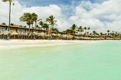 Beautiful View Of White Sand Aruba Beach. Blue Sunbeds Under Sun Umbrellas On Turquoise Water And Bl poster
