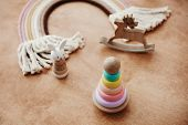 Stylish Wooden Toys For Child On Wooden Table. Modern Colorful Wooden Pyramid With Rings, Wooden Bun poster
