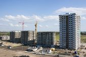 Apartment Buildings Under Construction. High-rise Apartment Buildings Under Construction And Crane A poster