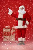 Full length portrait of the good old Santa Claus carrying gifts on a sleigh under a snowfall on a re poster