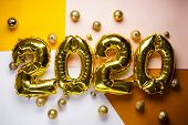 Celebrating The New Year 2020, Golden Foil Balloons 2020 On Colorful Backgrounds, With Golden Toys.  poster