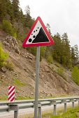 Road Sign - Falling Rocks. Road Sign falling Rocks On The Background Of A Mountain Road And A Rock poster