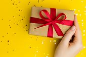 Brown Gift Boxes With Red Ribbons. Yellow Background With Multicolored Confetti. Flat Lay Style. Gif poster