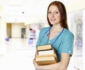 stock photo of hall  - Smiling female doctor with books in a hall of a hospital - JPG