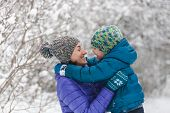 The Kid Hugs Mom. A Boy With His Mother On A Winter Walk. A Child In A Knitted Hat Kisses His Mother poster