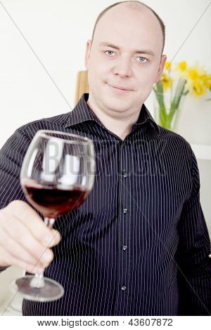 Man Raising His Glass In A Toast