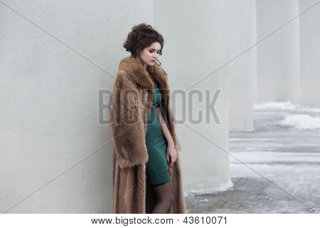 Glamour. Beauty Thoughtful Woman Over White Wall In Wool Outwear Dreaming
