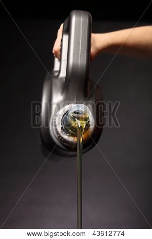Can With Car Engine Oil Pouring Black Background