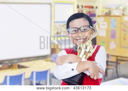Boy brings trophy in classroom