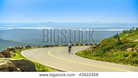 Female Mountain Bike Cyclist Riding Downhill Along Cadillac Mountain Road In Acadia National Park