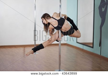 Young woman in pole fitness class