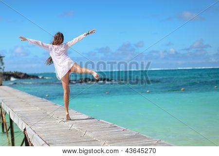 Rückansicht des schönen Mädchen, die zu Fuß am Strand wie ein Vogel