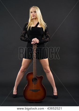 Female Standing With Acoustic Guitar