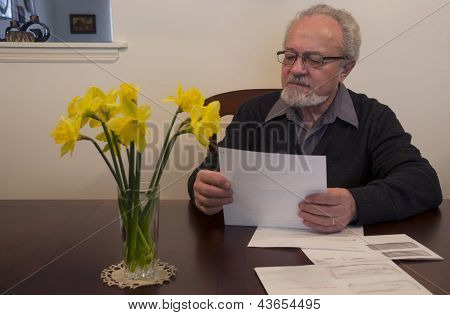Senior Man Looking Over Papers