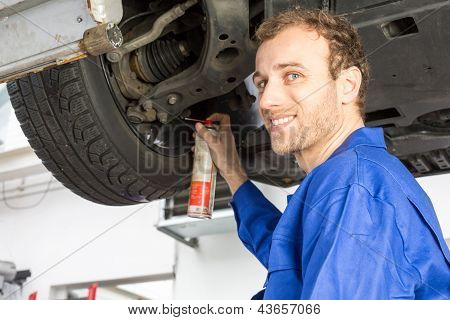 Mechanics Repairing A Car On Hydraulic Ramp