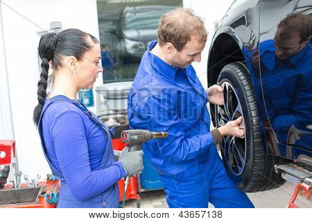 Two Mechanics Changing A Wheel On A Car