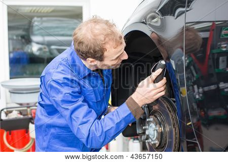 Car Mechanic Repairs The Brakes