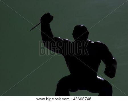 Black silhouette of a man wielding a knife