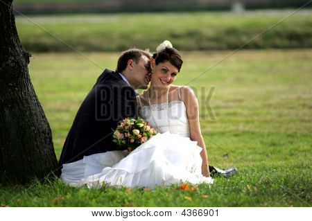 Newlywed Couple Kissing In Summer