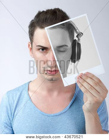 Young Male Holding Photo With Himself With Headphones