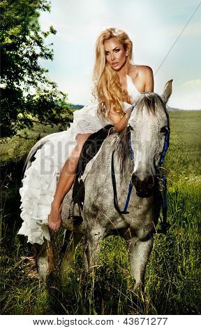 Young Blonde Bride Riding A Horse In Fashionable Dress.
