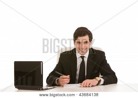 Businessman Writing At His Desk